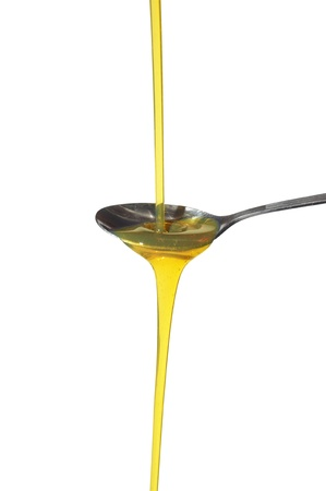sunflower oil on spoon on white background photo