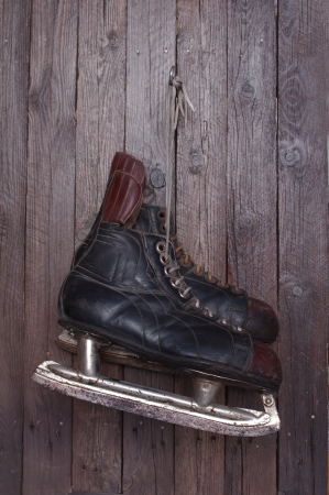 old hockey skates on background of wood photo