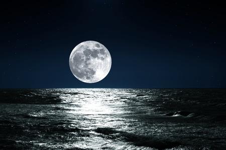 noche estrellada: la luna y su reflejo en el agua Foto de archivo