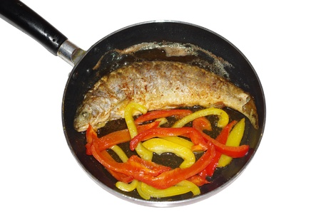 fried trout with vegetables   on frying pan photo