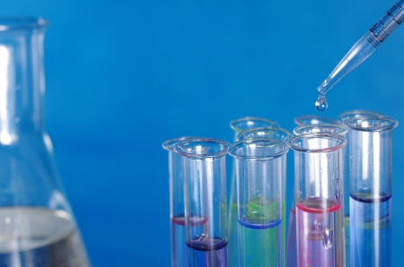 test-glass and pipette on blue background photo