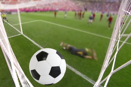 the foot ball in mesh of goal on background of stadium photo