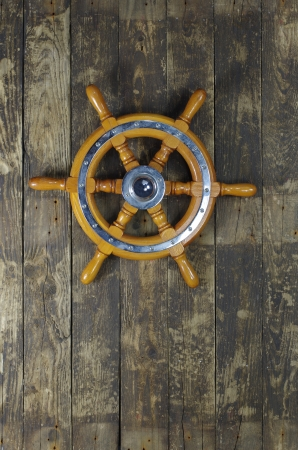 steering wheel of sailing-ship on a board background Banque d'images