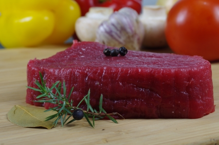 horseflesh: raw steak with vegetable on wooden board  Stock Photo