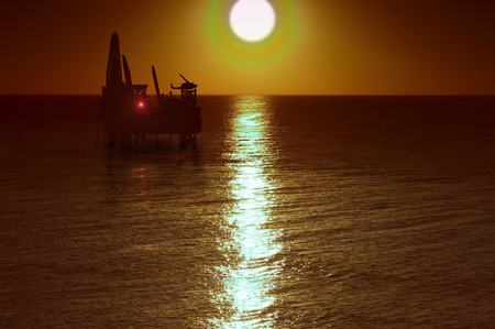 curren: the drilling platform on sea on background of the setting sun