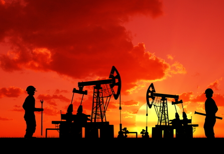 machine oil: two man on oilfield with pump on sunset background
