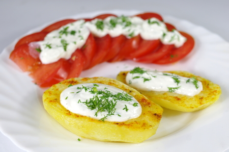 baked potato with cottage cheese, chives and tomatoes on a white plate  photo