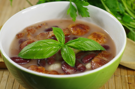 appetizing bean soup with meat and basil photo