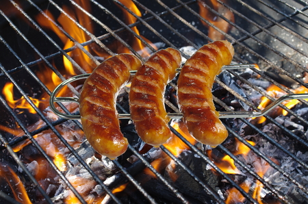 sausages on fork on barbeque background photo
