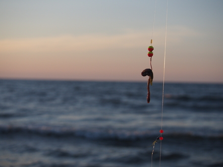 worm gear: fishing-rod with bait on sea background