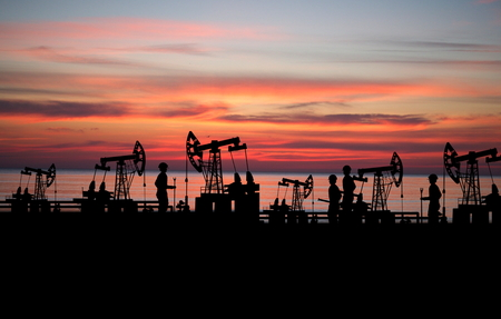 oilfield: two man on oilfield with pump on sunset background