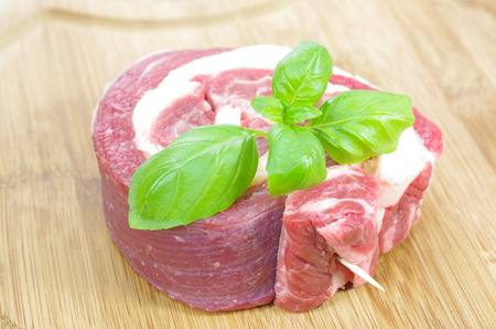horseflesh: coiled raw beef with basil on cutting board Stock Photo