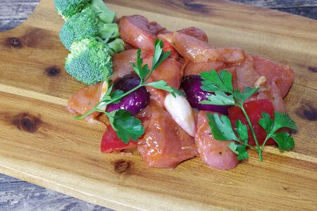 chicken meat with vegetables on wooden board