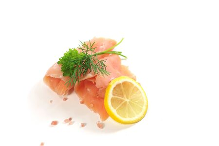 slices of smoked salmon with dill on white background