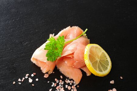 slices of smoked salmon with dill black plate background