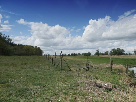 fenced empty pasture against the sky