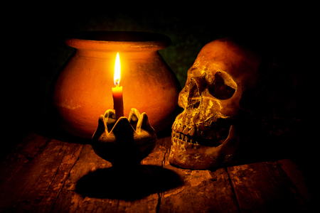 still life with Skull and candle with candlestick on wooden background