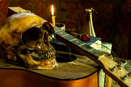 bespectacled: Still life with human skull bespectacled on guitar background