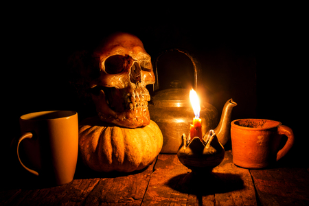 yellow teeth: Skull and candle with candlestick on wooden background, still life concept