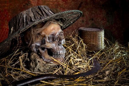 skull cap: Still life with  skull cap machine weave on straw and sickle,rice kratib Stock Photo