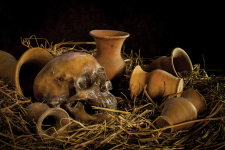 Still life with human a skull on straw and vase