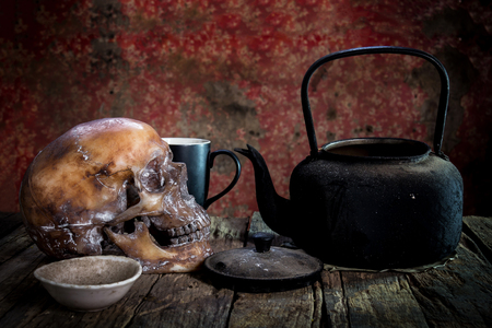 cadaver: Still Life with a Skull and kettle,cup,glass on wood