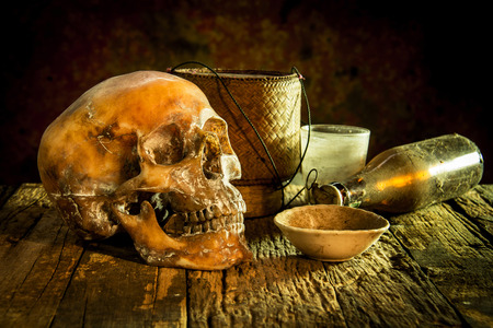 cadaver: Still Life with a Skull and cup,glass,bottle,kratib rice on wooden Stock Photo
