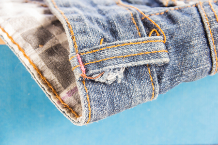 jeans stacked on a wooden background.Blue jeans on a brown wooden background.Frayed jeans.Detail of nice blue jeans with leather belt in vintage style.Texture of blue jeans background