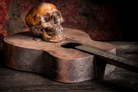 Still life with human skull on guitar background