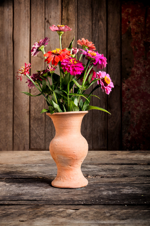cadaver: Still Life with a vase flower,earthenware on wooden Stock Photo