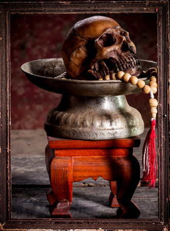 exorcist: still life with human skull rosary on the old wooden floor.