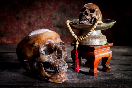 still life with human skull rosary on the old wooden floor.