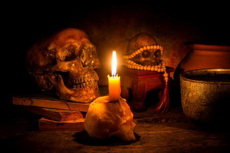 Skull and candle with candlelight on wooden background, still life concept