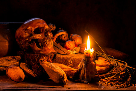 Skull and candle with candlestick on wooden background, still life concept