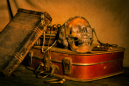 Still life with human skull with old treasure chest and gold, diamond and jewelry on wooden background Stock Photo