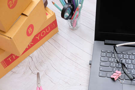 Cardboard parcel box for online selling. Packing accessories at workplace of startup small business owner, copy space