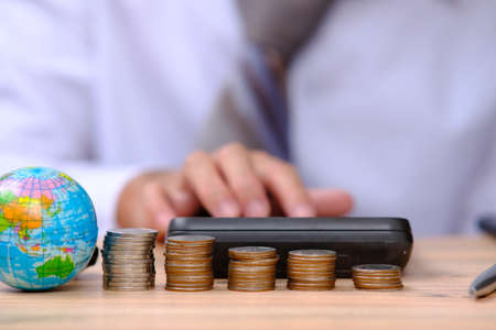 Businessman using caculator income saving money and investment concept. Money coin stack growing graph Balance savings Interest and Advertising coins of finance and banking