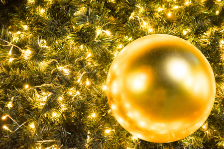 Christmas glod ball on the branches fir glowing garland , Christmas or New Years background.