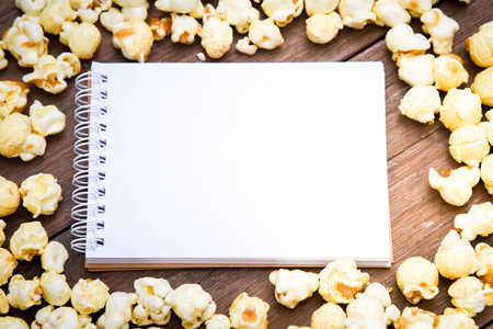 A bowl of popcorn and notebook  on a wooden table