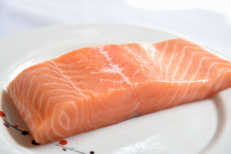 Salmon in white dish on white blackground.