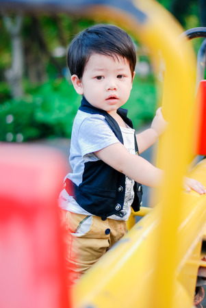 Cute little  Asian boy having fun on a playground outdoors , Happy kids