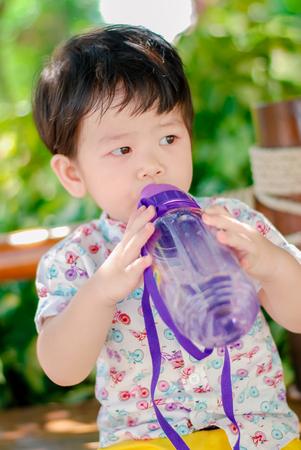 Cute little  Asian boy Happy smilling eat water  in the park outdoors , Happy kids