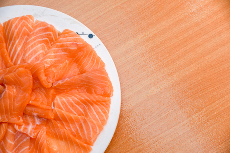 Closeup top view Slided Raw Salmon in white dish on wood blackground