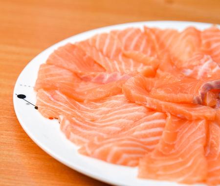Slided Raw Salmon in white dish on wood blackground