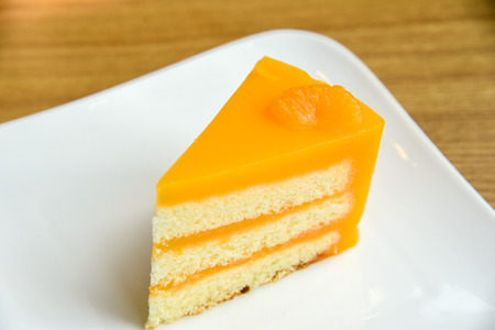 Orange cake in a white plate on wooden background ,  fruit cake