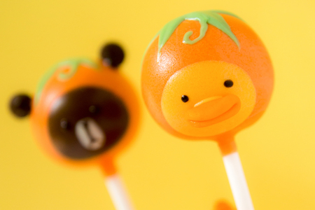 chick and bear cake pops in cup on orange background