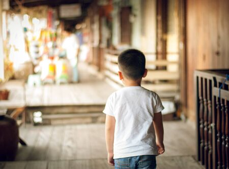 Kid boy wearing sweatshirt over isolated background walking backwards looking away . He is trying to look for the place and he couldt find it concept.Blurred market outdoor background. Stockfoto