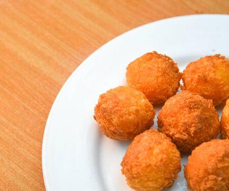 Cheese balls, Breaded mozzarella cheese balls with tomato in white dish on wood blackground