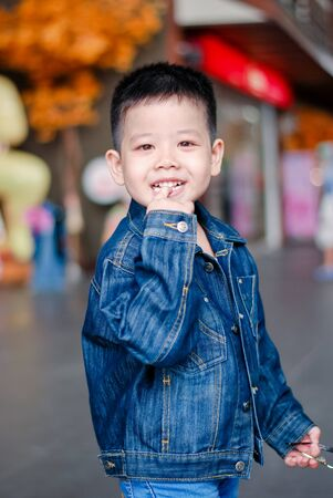 Portrait of little boy dressed jeans jacket smiles at the camera at park in the summer with smiling face. Fashion kid denim , Asia kid Stockfoto