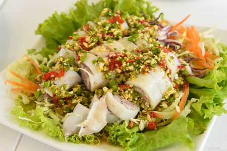 Spicy salad with squid and mix vegetables in white dish on white table at restaurant Stockfoto